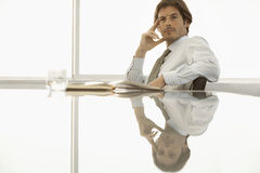 Confident Businessman Sitting At Conference Table Royalty Free Stock Image
