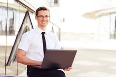 Confident businessman sitting with laptop Stock Photography