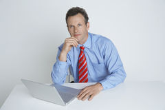 Confident Businessman Sitting With Laptop At Desk Stock Image
