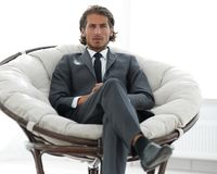 Confident businessman sitting in a large comfortable chair. Photo with copy space Stock Photos