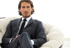 Confident businessman sitting in a large comfortable chair. Photo with copy space Royalty Free Stock Image