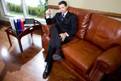 Confident businessman sitting on leather couch Stock Photos