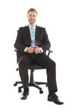 Confident businessman sitting on office chair Stock Images
