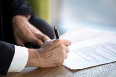 Close up male hands puts his signature on official document. Confident businessman sitting in office desk holding pen puts his signature on official document royalty free stock photos