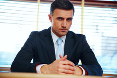 Confident businessman sitting at the table Stock Image
