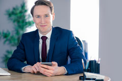Confident businessman with smartphone looking at camera Stock Photos