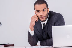 Confident businessman. Smiling African businessman sitting at th Stock Photos