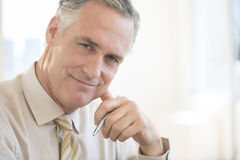 Confident Businessman Smiling In Office Royalty Free Stock Photo