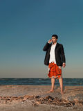 Confident businessman smoking cigar on sea shore Stock Photos