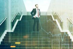 Confident businessman on staircase graphs. Confident bearded businessman standing with his arms on the waist on a staircase in a city. Graphs. 3d rendering toned Royalty Free Stock Photo