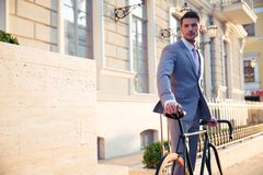 Confident businessman standing with bicycle Royalty Free Stock Photography