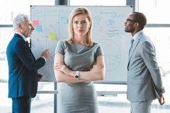 confident businessman standing with crossed arms and looking at camera while multiethnic businessmen standing at whiteboard stock photography