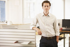 Confident Businessman Standing By Cubicle Stock Photos