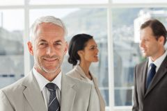 Confident businessman standing in front of colleagues speaking t Stock Photo