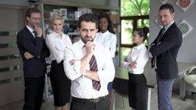 Confident businessman standing in front of his successful team. Concentrated Businessman Touches His Chin With One Hand While Standing In Front Of His Colleagues stock footage