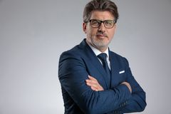 Confident businessman standing with his hands folded at his chest. While wearing a blue suit and glasses, posing on gray studio background royalty free stock photos