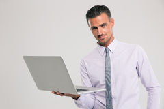 Confident businessman standing with laptop computer Royalty Free Stock Image