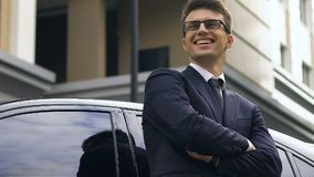 Confident businessman standing near car and happily smiling, successful deal. Stock footage stock video