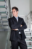 Confident Businessman Standing On Stairs. Confident businessman with arms crossed standing on stairs Stock Image