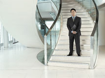 Confident Businessman Standing On Stairs. Full length portrait of a confident businessman with folder standing on stairs Stock Photography