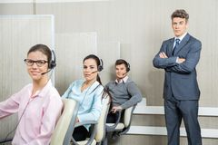 Confident Businessman Standing By Team In Call Stock Photos