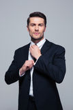 Confident businessman straightening his tie Stock Images