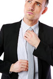 Confident businessman straightening his tie Royalty Free Stock Photos