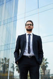 Confident businessman in stylish suit stands near a high-rise modern building Royalty Free Stock Photo
