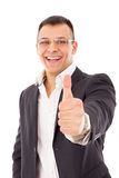 Confident businessman in suit with glasses showing thumbs up Stock Photos