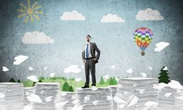 Successful confident businessman in suit. Confident businessman in suit standing on pile of documents among flying paper planes with drawn landscape on stock illustration