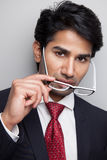 Confident businessman taking of glasses Stock Image