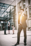 Confident businessman talking on mobile phone. In office premises Royalty Free Stock Photos