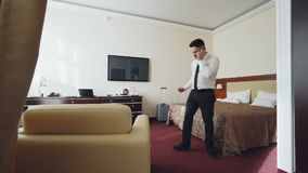 Confident businessman talking on mobile phone while walking around hotel room. Travel, business and people concept. Confident young businessman talking on mobile stock video