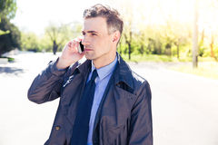 Confident businessman talking on the phone outdoors Stock Image