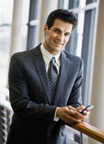Confident businessman text messaging on cell phone. In office lobby Stock Photos