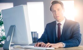 Confident businessman typing on computer and looking at camera Royalty Free Stock Image
