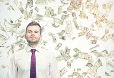 Confident businessman under dollar bill rain on sunny day Royalty Free Stock Photos