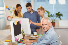 Confident businessman using on computer with colleagues in background Stock Image