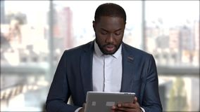 Confident businessman using digital tablet. Dark-skinned man in business suit working on pc tablet and talking on blurred background stock video
