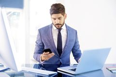 Confident businessman using his mobile phone and text messaging royalty free stock image