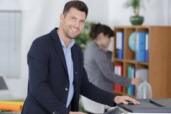 Confident businessman using printer in office. Businessman stock photography