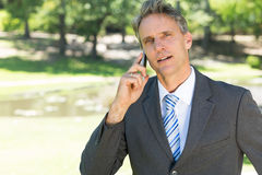 Confident businessman using smart phone Stock Photography