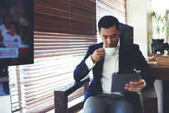 Confident businessman using touch pad for remote work while enjoying rest during coffee break Royalty Free Stock Image