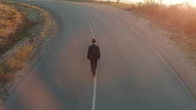 Man in suit walking straight by the road stock video footage