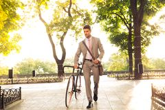 Confident businessman walking with bicycle Royalty Free Stock Image