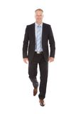 Confident Businessman Walking Over White Background Royalty Free Stock Image