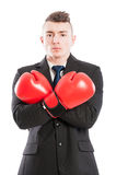 Confident businessman wearing boxing gloves and arms crossed. Confident and powerful businessman wearing boxing gloves and arms crossed standing isolated on Stock Image