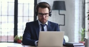 Confident businessman wears headset making conference video call on laptop