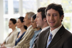 Confident Businessman With Team Walking Past Him Royalty Free Stock Image