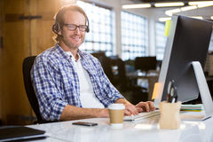Confident businessman working at computer desk Stock Image